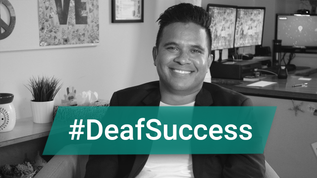 """Carlos Aponte-Salcedo, a man wearing a white shirt and black jacket, smiles at the camera. Text reads """"#DeafSuccess"""""""