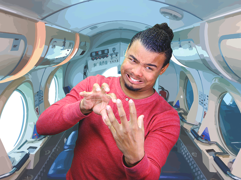 Justin Perez, a black man with long curly black hair pulled back into a bun, a chin goatee, and a red long-sleeved shirt stands in the interior of a spaceship. He faces the camera and is very expressive as he tilts to the right and signs something with two hands facing each other. The interior of the spaceship looks like a long shiny white rounded hallway. There are several large round windows along each wall. One side shows light coming in while the other side is dark. The floor is dark blue with rows of small lights on either side. Near the ceiling are rows of overhead bins with closed doors. The wall behind Justin displays symbols in black, white, and red and there is something that looks like a smoke detector on the ceiling.