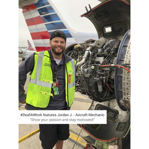 Man with light skin and brown hair and close-cut beard stands smiling at the camera next to an open engine of a smaller white airplane. He wears a black baseball cap backwards, a neon yellow safety vest over a grey long sleeve henley with a white shirt underneath and black shorts.