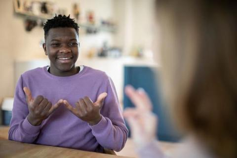 "Black Teen signs ""now"" while smiling at an out-of-focus woman."