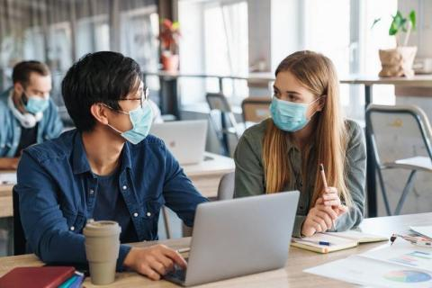 Two students, an Asian man and a white woman, in protective mask talking while studying with laptop