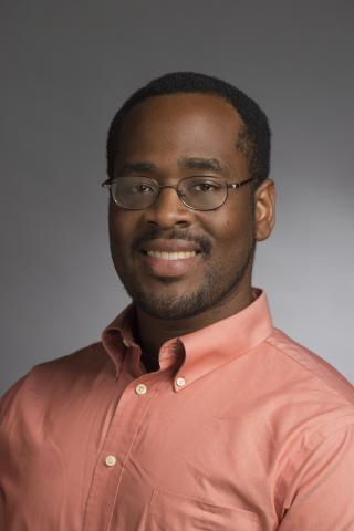 Dr. Joseph Hill, a black man wearing glasses and a peach shirt, smiles in front of a gray background