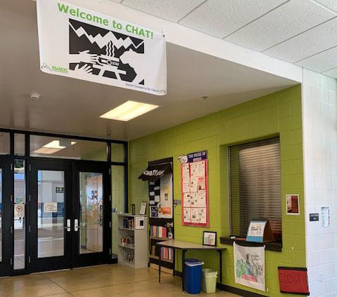 """A hallway with one wall painted green, and a closed service window. Above the hallway hangs a sign that reads """"Welcome to CHAT!"""" with a black and white illustration of hands and a cat reaching for a cup of coffee."""
