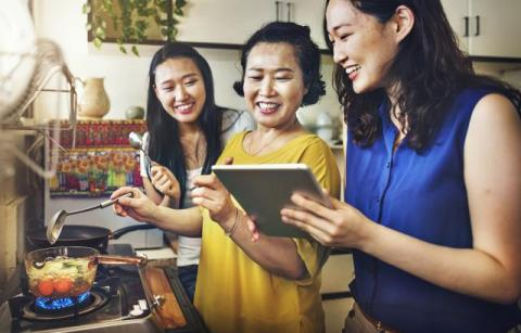 Two smiling asian teens in the kitchen with their mother between them, all looking at a tablet.