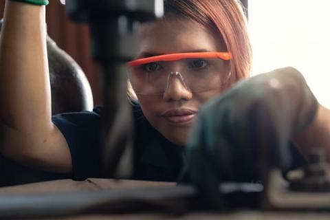 young female person of color staring carefully at a drill bit of a larger machine