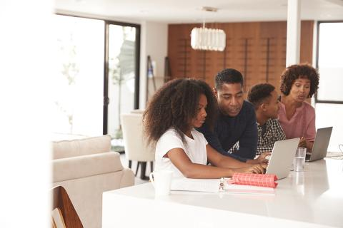 Two Black teens on laptops with their parents. A teen girl is helped by her father, and a teen boy helped by his mother.