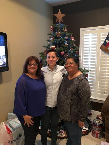 Diego Guerra, a Mexican-American wearing a white shirt stands between two Mexican-American women with a Christmas tree in the background. Diego said Tia Belinda and Tia Juanita work hard to ensure Diego is included in family gatherings.