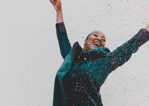 Photo of a Black woman smiling widely and throwing her arms up in the air as confetti floats down around her. She wears a dark green velvet blazer. Background is grey.