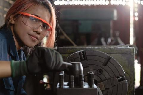 A young multiracial woman poses with heavy machinery.